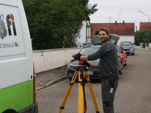 Monteur am Nivelliergerät zur Übertragung der von der Behörde/Gemeinde erhaltenen Ausgangspunkte/Fixpunkte für die Höhenangabe