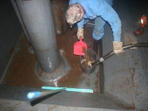 Monteur bei der Reinigung des Pumpensumpf