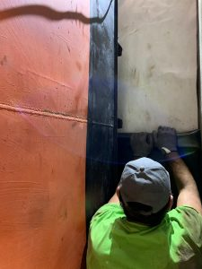 Monteur beim Einbringen der Folie im Bodenbereich unter den angehobenen Tank